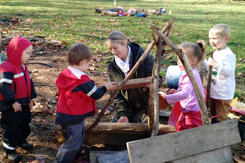Students work together to enclose a stick house they have built.